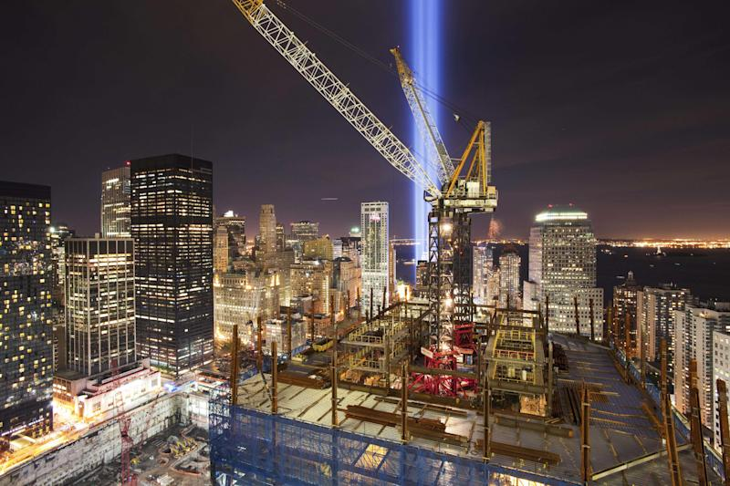 """FILE - In this Sept. 11, 2010 file photo, the """"Tribute in Light"""" shines above the construction cranes on One World Trade Center, and the lower New York skyline. In an annual tradition, the two bright blue beams of light are projected from lower Manhattan, in memory of the fallen twin towers. On World Trade Center's spire was fully installed atop One World Trade Center on Friday, May 10, 2013, bringing the New York City structure to its symbolic height of 1,776 feet. (AP Photo/Mark Lennihan, File)"""
