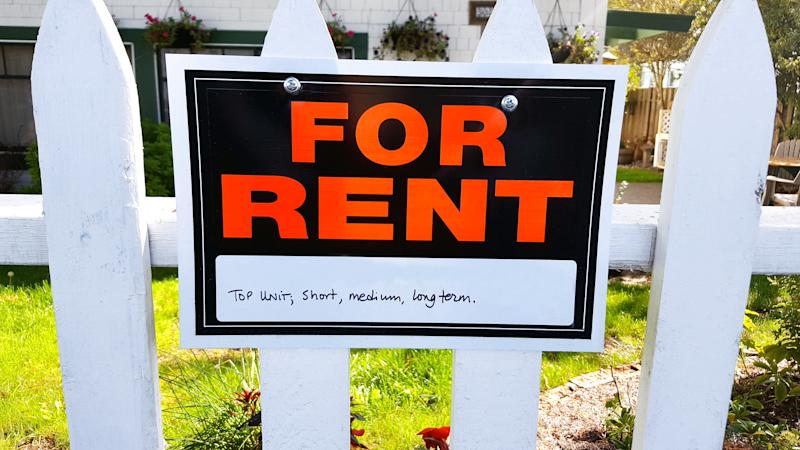Close up of For Rent sign on white picket fence in front yard of house.