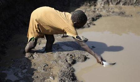 Sudanese girl collects water from muddy pond in South Sudan's Doro refugee camp