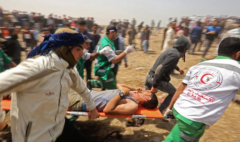 Palestinians evacuate an injured protester during clashes with Israeli security forces near the Gaza border fence on April 13, 2018 (AFP Photo/MAHMUD HAMS)