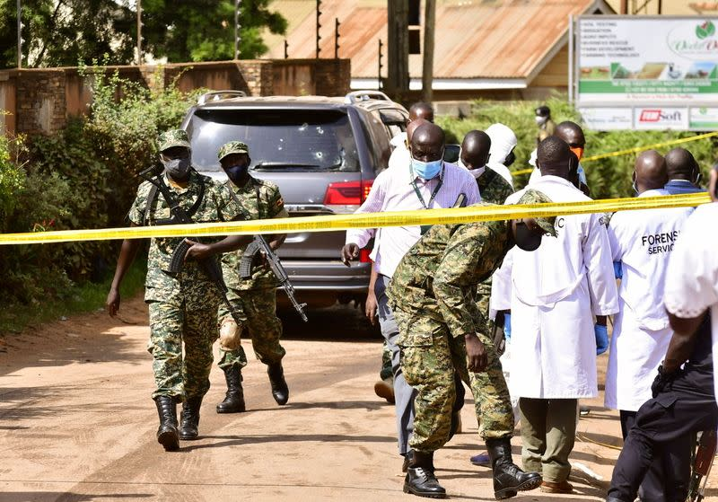 Security forces and forensic experts secure the scene of an attempted assassination on Ugandan minister of works and transport General Katumba Wamala in the suburb of Kiasasi within Kampala