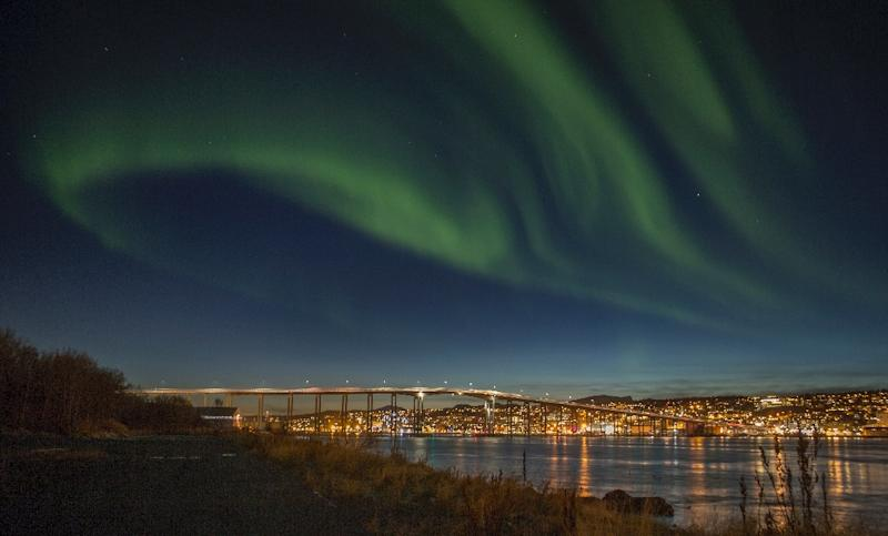 Northern lights (Aurora borelias) are seen on October 20, 2014 over the Norwegian city of Tromsoe, close to a former NATO naval base now sheltering Russian ships