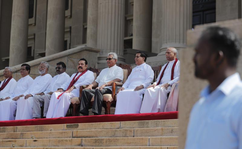 Sri Lankan president Gotabaya Rajapaksa, seated third right, sits for photographs with his new cabinet members in Colombo, Sri Lanka, Friday, Nov. 22, 2019. Rajapaksa, who was elected last week, said he would call a parliamentary election as early as allowed. The parliamentary term ends next August, and the constitution allows the president to dissolve Parliament in March and go for an election. (AP Photo/Eranga Jayawardena)