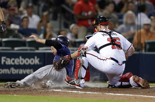 Colorado Rockies' Michael Cuddyer (3) is tagged out by Atlanta Braves catcher Brian McCann (16) as he tried to score on a Wilin Rosario double in the seventh inning of a baseball game in Atlanta, Tuesday, July 30, 2013. (AP Photo/John Bazemore)