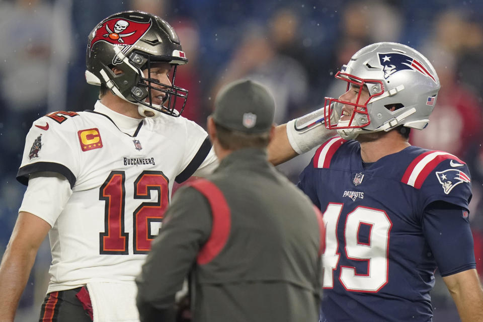 Tampa Bay Buccaneers quarterback Tom Brady (12) meets with New England Patriots long snapper Joe Cardona (49) prior to an NFL football game between the New England Patriots and Tampa Bay Buccaneers, Sunday, Oct. 3, 2021, in Foxborough, Mass. (AP Photo/Steven Senne)