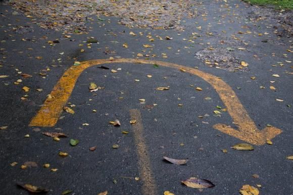 A U-turn sign painted on the pavement.