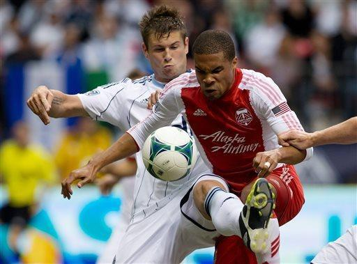 Vancouver Whitecaps' Brad Rusin, left, defends against Portland Timbers' Ryan Johnson, of Jamaica, during the first half of an MLS soccer game in Vancouver, British Columbia on Saturday, May 18, 2013. (AP Photo/ The Canadian Press, Darryl Dyck)