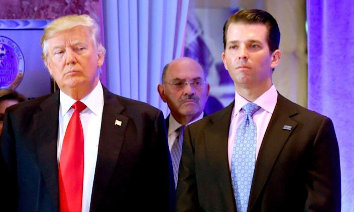 Allen Weisselberg stands behind Donald Trump and his son Don Jr.