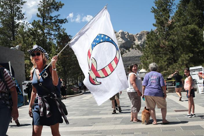 "A Donald Trump supporter holding a QAnon flag visits Mount Rushmore National Monument on July 01, 2020 in Keystone, South Dakota. <p class=""copyright"">Photo by Scott Olson/Getty Images</p>"