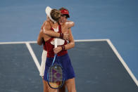 Belinda Bencic, of Switzerland, is hugged by Marketa Vondrousova, of the Czech Republic, following the women's gold medal match of the tennis competition at the 2020 Summer Olympics, Saturday, July 31, 2021, in Tokyo, Japan. Bencic won the match. (AP Photo/Seth Wenig)