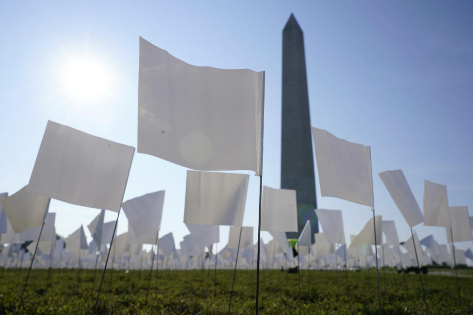 """White flags stand near the Washington Monument on the National Mall in Washington, Wednesday, Sept. 15, 2021. The flags, which will number more than 630,000 when completed, are part of artist Suzanne Brennan Firstenberg's temporary art installation, """"In America: Remember,"""" in remembrance of Americans who have died of COVID-19. (AP Photo/Patrick Semansky)"""