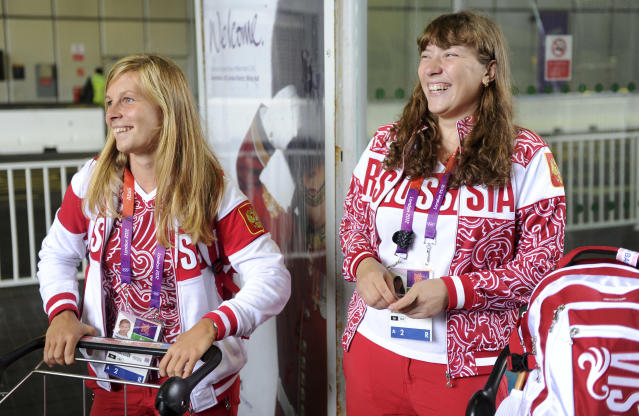 Tatiana Bazyuk (L) and Svetlana Shnitko part of the Russian Olympic sailing squad smile as they wait to board a bus after arriving at Heathrow airport, London, July 16, 2012. The Lndon 2012 Olympic Games start in 11 days time. REUTERS/Paul Hackett (BRITAIN - Tags: SPORT OLYMPICS)