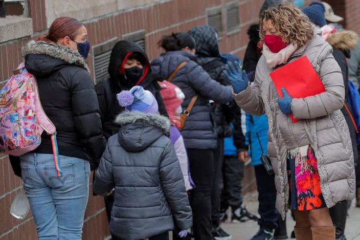 FILE PHOTO: A principal greets students as they return to New York City's public schools for in-person learning at P.S. 506 in Brooklyn, New York