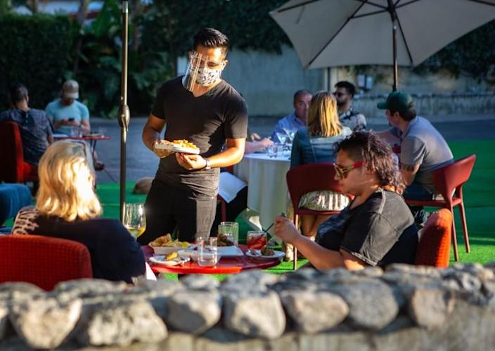 LOS ANGELES, CA - JULY 08: People have drinks and dine on the outdoor patio at La Boheme in West Hollywood as coronavirus surges on Wednesday, July 8, 2020 in Los Angeles, CA. Bars and indoor dining could remain closed for the foreseeable future in Los Angeles. (Jason Armond / Los Angeles Times)