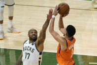 Milwaukee Bucks forward P.J. Tucker (17) tries to block a shot by Phoenix Suns guard Devin Booker (1) during the second half of Game 4 of basketball's NBA Finals in Milwaukee, Wednesday, July 14, 2021. (AP Photo/Paul Sancya)