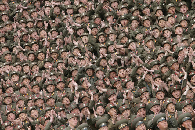 <p>Soldier-builders of KPA Units 966, 462, 101, 489, who took part in building the workers' hostel of Kim Jong Suk Pyongyang Textile Mill, applaud during a photo session with North Korean leader Kim Jong Un in this undated photo. (KCNA/Reuters) </p>