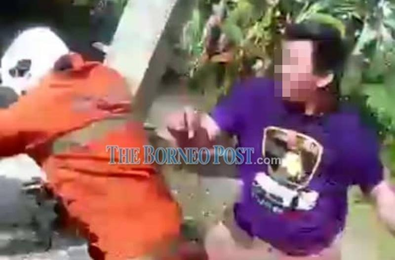 A screengrab from a video showing a civilian attacking a firefighter who was dousing the flames at a house n Kampung Belipat, Lawas last Saturday. — Picture via Borneo Post