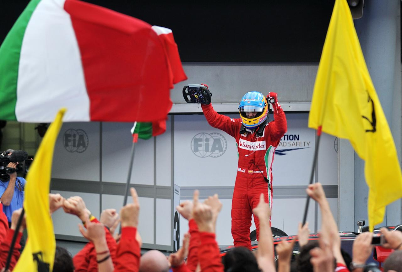 Ferrari driver Fernando Alonso of Spain celebrates after winning Formula One's Malaysian Grand Prix at the Sepang International Circuit in Sepang on March 25, 2012. TOPSHOTS  AFP PHOTO / ROSLAN RAHMAN (Photo credit should read ROSLAN RAHMAN/AFP/Getty Images)
