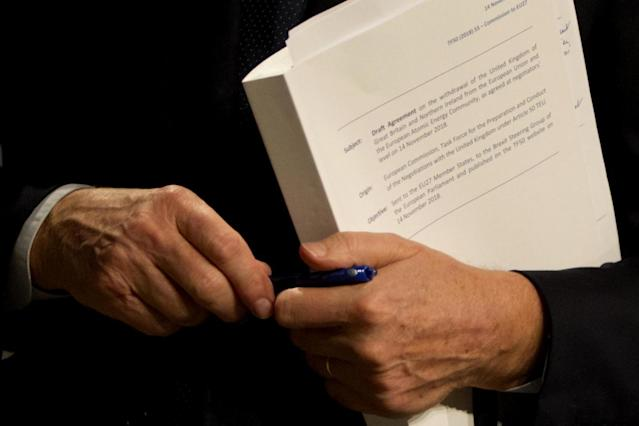 EU chief Brexit negotiator Michel Barnier holds the draft withdrawal agreement (AP)