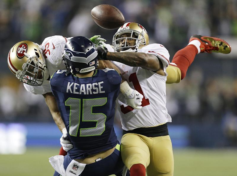 San Francisco 49ers' Eric Reid (35) and Donte Whitner (31) break up a pass intended for Seattle Seahawks' Jermaine Kearse during the second half of the NFL football NFC Championship game Sunday, Jan. 19, 2014, in Seattle. (AP Photo/Marcio Jose Sanchez)
