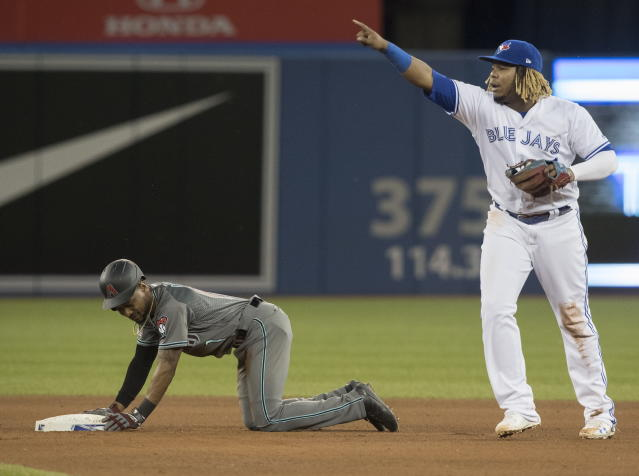 Toronto Blue Jays' Vladimir Guerrero Jr. gestures to dugout for a review of play at second base with Arizona Diamondbacks Jarrod Dyson stealing in the seventh inning of a baseball game Friday, June 7, 2019, in Toronto. The play was reviewed, and Dyson was ruled safe. (Fred Thornhill/The Canadian Press via AP)