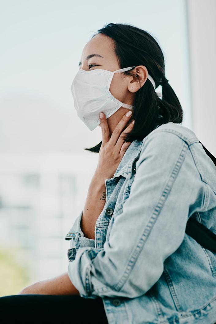 Shot of a young woman wearing a mask and suffering from throat pain in a doctor's office