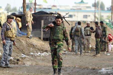A Shi'ite fighter walks during an intensive security deployment against Islamic State militants