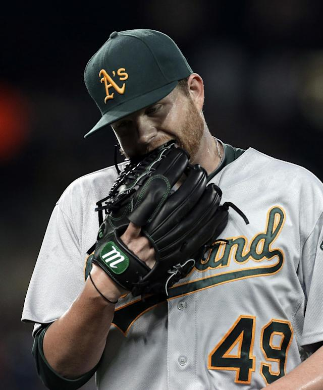 Oakland Athletics pitcher Brett Anderson bites his glove after pitching against the Detroit Tigers in the seventh inning of a baseball game in Detroit, Wednesday, Aug. 28, 2013. (AP Photo/Paul Sancya)