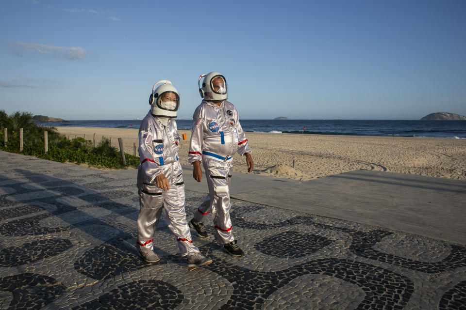 """Tercio and Alicea Galdino, dressed in astronaut costumes, walk along Ipanema beach in Rio de Janeiro, Brazil, Saturday, March 20, 2021. The Galdinos have come up with a unique way for protecting themselves and drawing awareness around COVID-19 protective measures – by dressing as astronauts. The pair first began to traverse the iconic beaches fully suited in mid 2020 at the height of the first wave of the pandemic in Brazil, now as cases surge once again they are taking their """"astronaut walks"""" back to the promenades. (AP Photo/Bruna Prado)"""