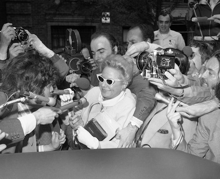 """<p>Martha Mitchell carries a worn Bible as she makes her way through a throng of newsmen to give a deposition about the Watergate case to a lawyer in New York City on May 3, 1973. """"I wouldn't want to have to swear on a dictionary,"""" quipped the wife of former Attorney General John Mitchell. (Photo: AP) </p>"""
