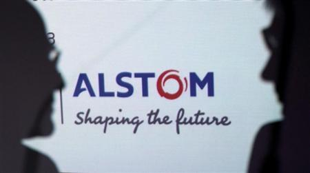 People are silhouetted in front on an Alstom logo during a news conference to present the group's first half results at the company headquarters in Levallois-Perret