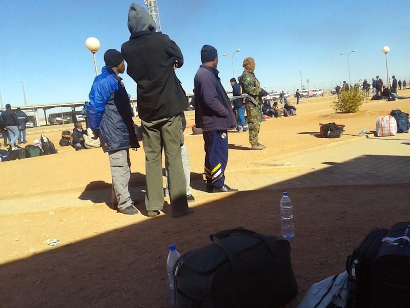 In this Jan. 16, 2013 photo secretly taken by a hostage, an Islamic militant, in camouflage uniform, rear right, stands near Algerian employees who were forced to leave their houses with their belongings at the Ain Amenas natural gas complex in Ain Amenas, Algeria. (AP Photo/Kyodo News) JAPAN OUT, MANDATORY CREDIT, NO LICENSING IN CHINA, HONG KONG, JAPAN, SOUTH KOREA AND FRANCE