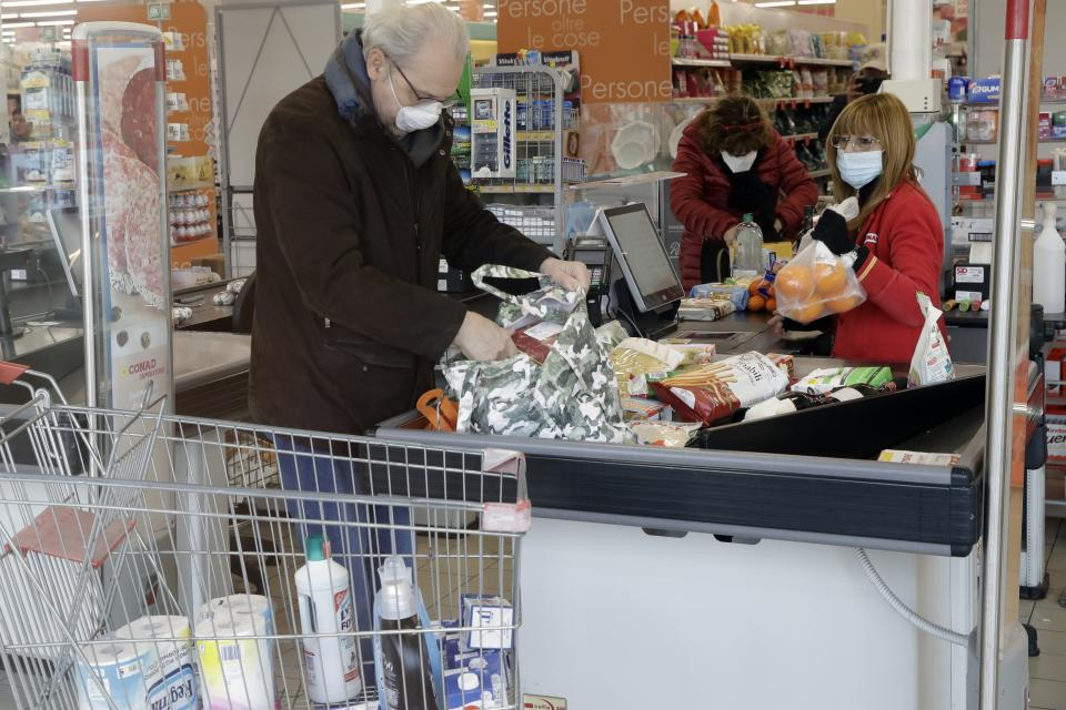 Clients and a cashier wear sanitary masks in a supermarket in Casalpusterlengo, Italy, Sunday, Feb. 23, 2020. A dozen Italian towns saw daily life disrupted after the deaths of two people infected with the virus from China and a pair of case clusters without direct links to the outbreak abroad. A rapid spike in infections prompted authorities in the northern Lombardy and Veneto regions to close schools, businesses and restaurants and to cancel sporting events and Masses. (AP Photo/Luca Bruno)