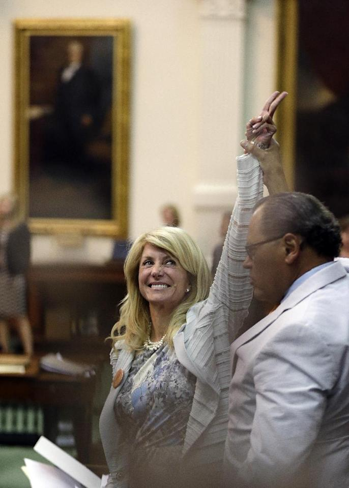 File - In this June 26, 2013 file photo, Sen. Wendy Davis, D-Fort Worth, left, celebrates as time runs out on an abortion bill, in Austin, Texas. Davis' compelling personal story of rising from a trailer park to Harvard Law has reeled in donors. She now has financial backers in every U.S. state. (AP Photo/Eric Gay, File)