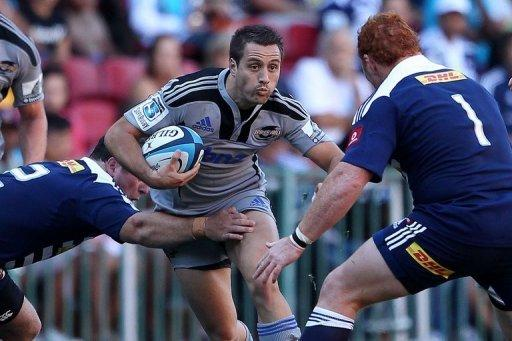 Andre Taylor of the Hurricanes (C) tries to break the defence during a Super 15 Rugby match in February 2012
