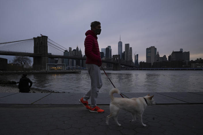 A man wearing a mask walks his dog in Brooklyn Bridge Park on Tuesday during the coronavirus pandemic in New York.