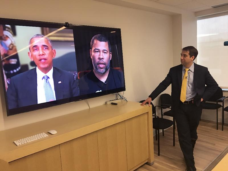 "Paul Scharre of the Center for a New American Security looks at a ""deepfake"" video of former US President Barack Obama manipulated to show him speaking words from actor Jordan Peele on January 24, 2019, in Washington (AFP Photo/Robert LEVER)"