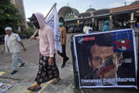 Muslim men walk past a defaced poster of French President Emmanuel Macron during a protest at Al Jihad mosque in Medan, North Sumatra, Indonesia, Friday, Oct. 30, 2020. Muslims around the world have been calling for both protests and a boycott of French goods in response to France's stance on caricatures of Islam's most revered prophet. (AP Photo/Binsar Bakkara)