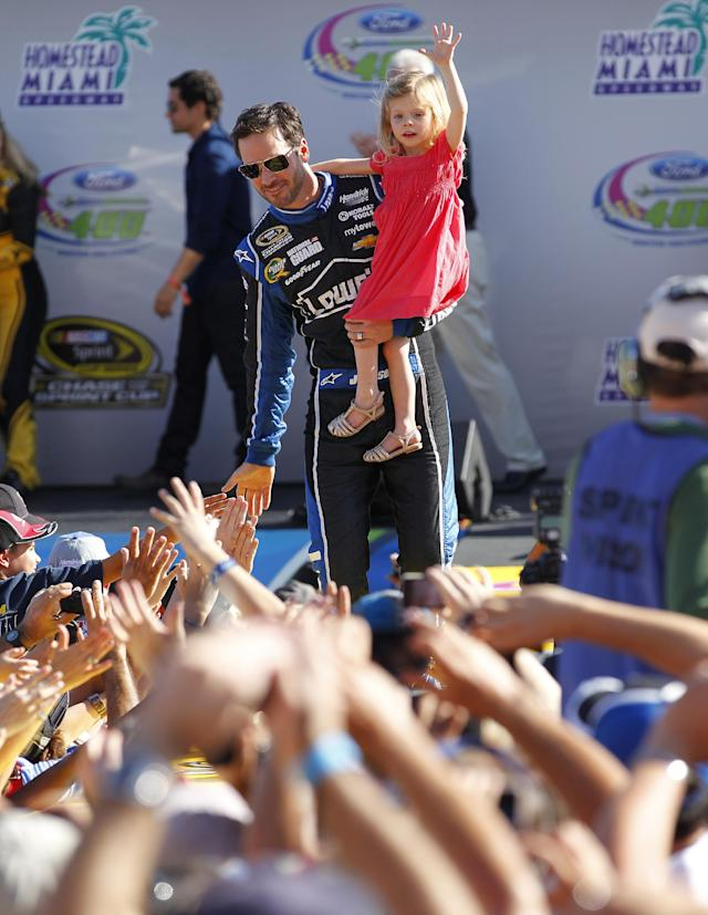 Jimmie Johnson with his daughter, Genevieve, greet fans during driver introductions before the NASCAR Sprint Cub Series auto race in Homestead, Fla., Sunday, Nov. 17, 2013. (AP Photo/J Pat Carter)