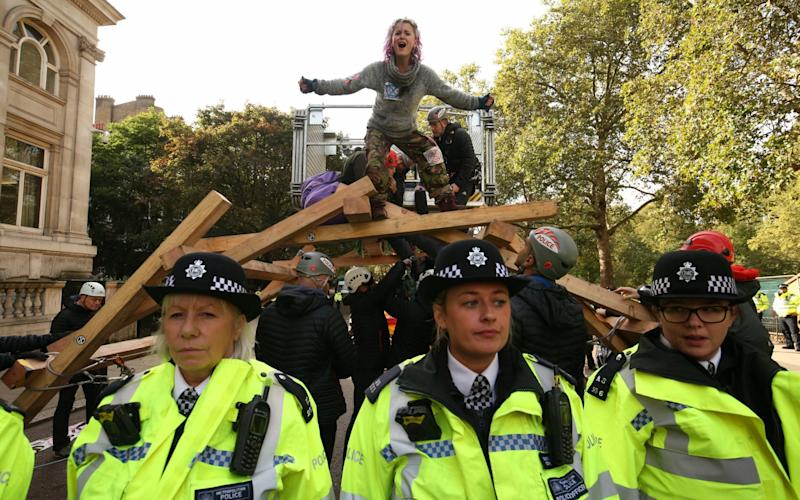 Police surround protesters on top of a wooden structure on Birdcage Walk  - PA