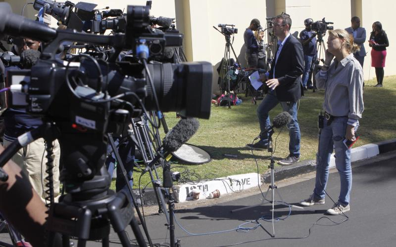 Broadcasters report live from outside the Johannesburg home of former president Nelson Mandela after he was discharged from a Pretoria hospital Sunday Sept. 1, 2013. Mandela has been in hospital for nearly months fighting a recurring lung infection. (AP Photo/Denis Farrell)