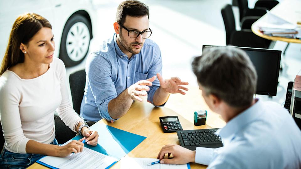 Above view of young couple communicating with car salesperson on a meeting in showroom.
