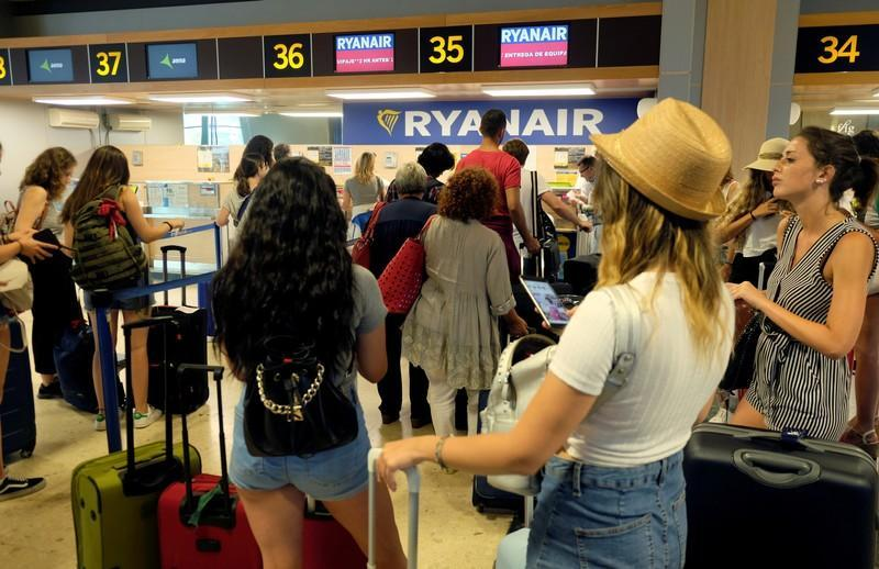 FILE PHOTO: Ryanair passengers line up to check in their luggage at the airport, during a protest on the second and last day of a cabin crew strike held in several European countries, in Valencia