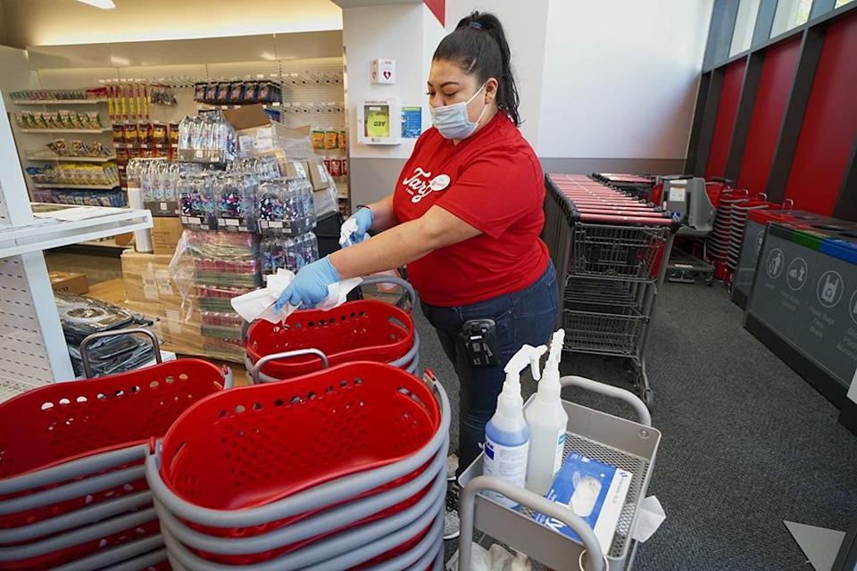 A worker sanitizes shopping carts at a Target store on campus at the University of California, San Diego. - Credit: Courtesy of Target