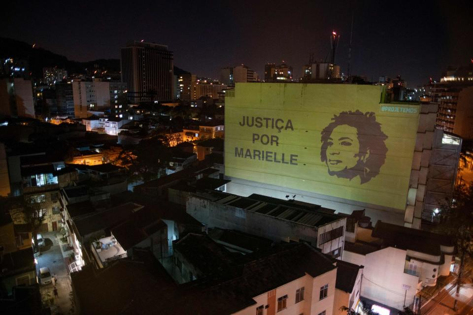"A projection on a building honouring slain councilwoman Marielle Franco reads ""Justice for Marielle,"" in Botafogo neighbourhood in Rio de Janeiro, Brazil, on August 8, 2020. - Franco, a popular leftist city councillor in Rio de Janeiro, was gunned down alongside her driver in March 2018 -- a drive-by shooting that investigators described as a ""summary execution."" (Photo by Mauro PIMENTEL / AFP) (Photo by MAURO PIMENTEL/AFP via Getty Images)"
