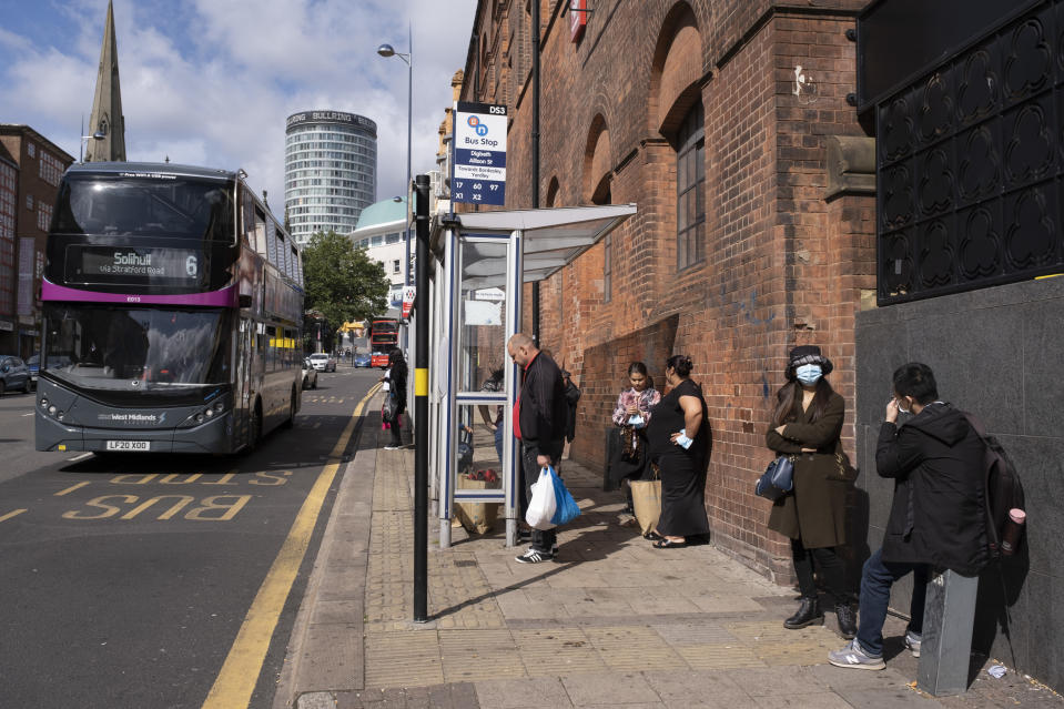 As numbers of Covid-19 cases in Birmingham have dramatically risen in the past week, increased lockdown measures have been announced for Birmingham and other areas of the West Midlands, people wearing face masks waiting at a bus stop a s abus to Solihull passes just outside the shopping district in the city centre on 12th September 2020 in Birmingham, United Kingdom. With the rule of six also being implemented the Birmingham area has now be escalated to an area of national intervention, with a ban on people socialising with people outside their own household, unless they are from the same support bubble. (photo by Mike Kemp/In Pictures via Getty Images)