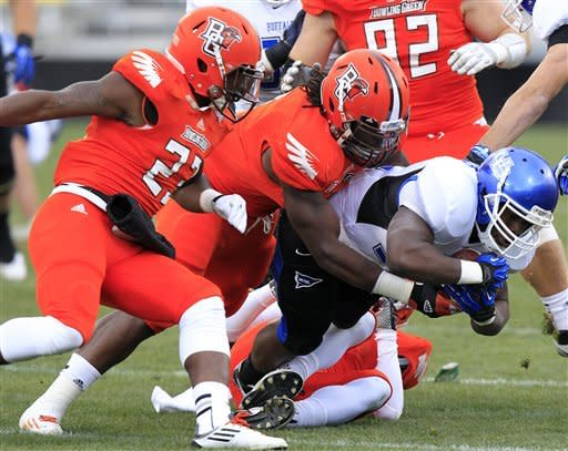 Buffalo running back Branden Oliver, right, is tackled by Bowling Green's Aaron Foster, left, and D.J. Lynch during the first quarter of an NCAA college football game Friday, Nov. 23, 2012, in Columbus, Ohio. (AP Photo/Jay LaPrete)