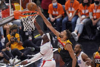 Utah Jazz center Rudy Gobert, center, defends against Los Angeles Clippers guard Reggie Jackson, left, during the first half of Game 2 of a second-round NBA basketball playoff series Thursday, June 10, 2021, in Salt Lake City. (AP Photo/Rick Bowmer)