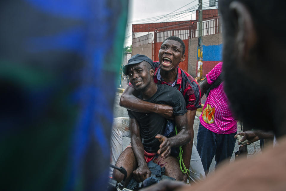 A protester who was hit in the leg by police fire is helped onto a motorcycle to be taken to the hospital, as police clash with demonstrators in Port-au-Prince, Haiti, Sept. 30, 2019. The image was part of a series of photographs by Associated Press photographers which was named a finalist for the 2020 Pulitzer Prize for Breaking News Photography. (AP Photo/Rebecca Blackwell)