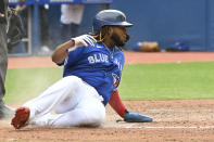 Toronto Blue Jays' Vladimir Guerrero Jr. slides safely into home following a single by Teoscar Hernandez during the fifth inning of a baseball game against the Tampa Bay Rays, Wednesday, Sept. 15, 2021 in Toronto. (Jon Blacker/The Canadian Press via AP)